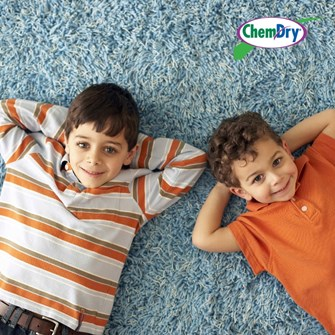 two young boys laying on clean carpet